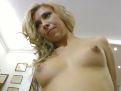 A blonde with a sexy smile is getting a penis inside her mouth
