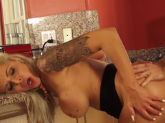 A blonde with tattoos feels her cunt getting penetrated in the kitchen