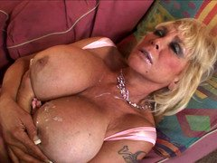A granny that has big saggy tits is getting cum over her body