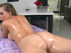 Blonde with large jugs is naked on the massage table, doing backdoor