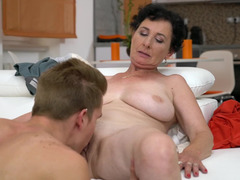A granny is kissing a young dude and she is getting her cunt licked