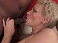 A black fella is penetrating a short haired granny on the bed