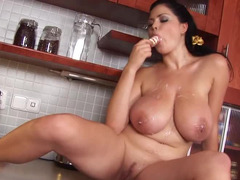 A fat gal is in the kitchen and besides she is playing with her sizeable boobs