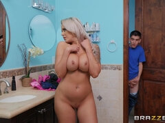 Busty blonde bends down in front of a strong lad in bathroom