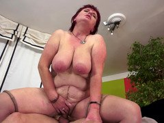 A big mature granny redhead with sizeable saggy breasts is getting rammed