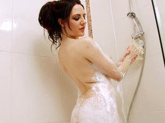 A nice-looking dame with large boobs is washing up in the shower with soap