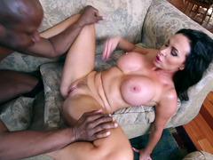 A milf with big boobs is sucking a black cock wit her mouth