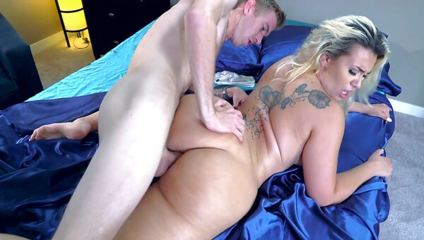 A big ass blonde with tattoos on her back is getting fucked on bed