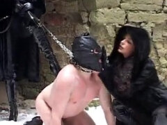 Two femdoms ballbusting and humiliating leashed slave in a dungeon