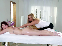 Two girls are on the massage table, getting covered with oil